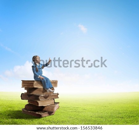 Image of cute school girl in sitting on pile of books - stock photo