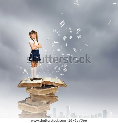 Image of cute school girl standing on pile of books - stock photo