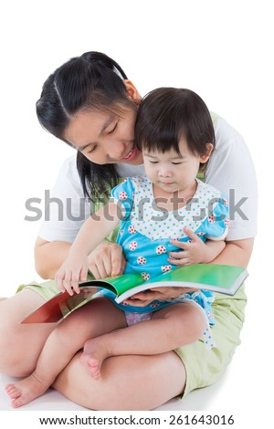 Image of cute young female with little asian (thai) girl reading a book together, daughter sitting on the lap, concept about development of reading in young children, isolated on white background - stock photo