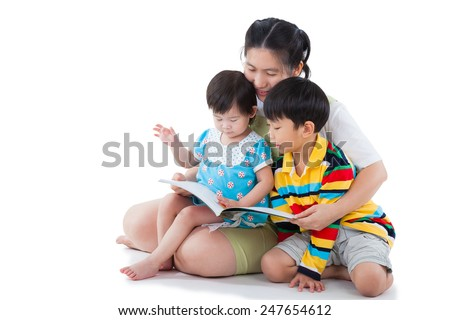 Image of cute young female with two little asian (thai) children reading a book together, daughter sitting on the lap, son sitting on the floor, happy family concept, isolated on white background - stock photo