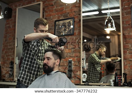 Image of cutting hair in a man's barber shop. The working day in Barbershop, stylish hipsters client with beard and mustache Stylist makes hair styling hair dryer. - stock photo