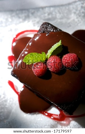 Image of decadent chocolate cake topped with raspberries - stock photo
