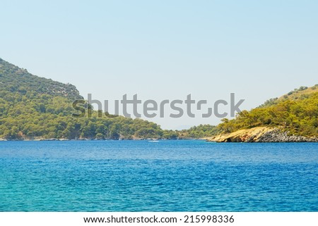 Image of deep blue sea with mountains and sky - stock photo