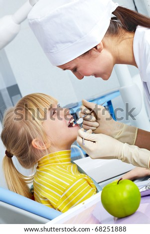 Image of dental checkup given to little girl by dentist - stock photo