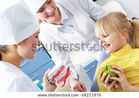 Image of dentist showing care dental hygiene to little girl with assistant near by - stock photo