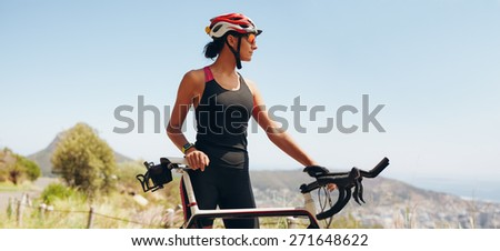 Image of determined female cyclist looking away. Fit woman wearing sportswear and cycling helmet looking at copyspace. - stock photo
