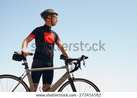 Image of determined male cyclist looking away while standing against sky. Fit man wearing sportswear and cycling helmet looking at copyspace. - stock photo