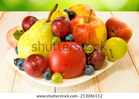 image of different fruits on a plate on a green background - stock photo