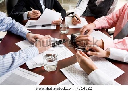 Image of different hands at business meeting - stock photo