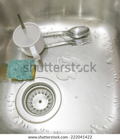 image of dirty sink with dirty cup,spoon,fork,and sponge . - stock photo
