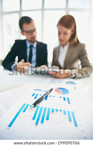 Image of document and pen at workplace and business partners networking on background - stock photo