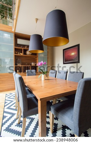 Image of eating room with wooden table and grey chairs - stock photo
