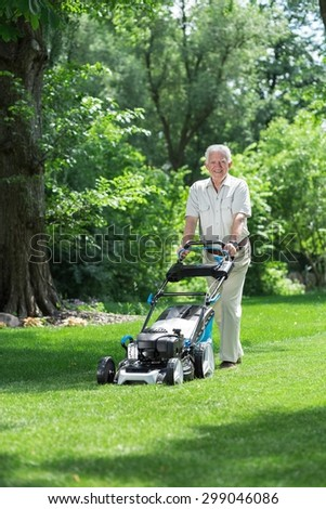 Image of elder gardener mowing green lawn
