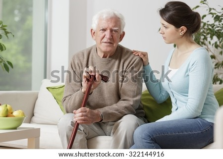 Image of elderly man with walking stick and his carer - stock photo