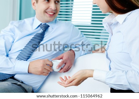 Image of elegant businessman and his pretty colleague interacting in office - stock photo