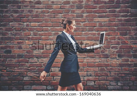 Image of elegant businesswoman with laptop walking along brick wall