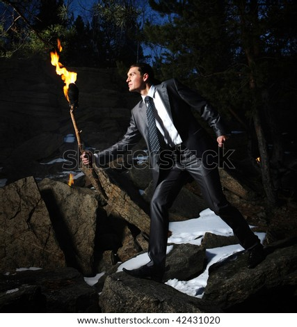 Image of elegant man holding burning stick while moving in darkness