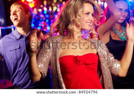 Image of energetic girl dancing on background of happy friends