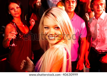 Image of energetic girl looking at camera on background of clubbers - stock photo