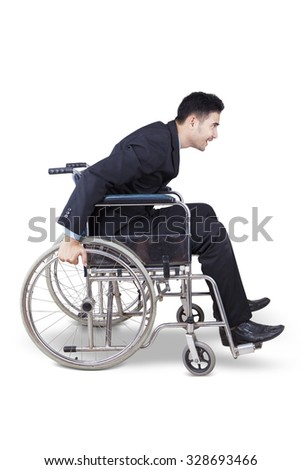 Image of enthusiasm disabled businessman sitting on the wheelchair and try to push it alone - stock photo