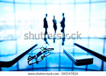 Image of eyeglasses, cellular phone and touchpads at workplace with businesspeople standing on the background