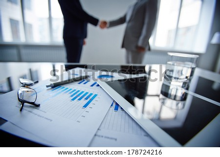 Image of eyeglasses, glass of water, touchpad and financial documents at workplace with businessmen handshaking on background - stock photo