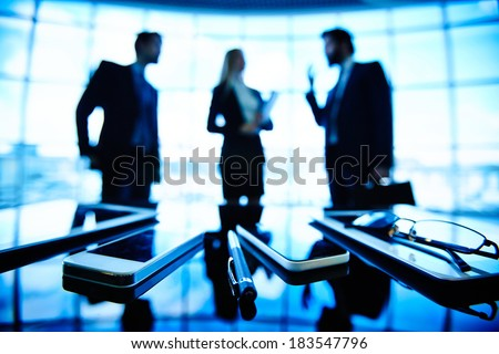 Image of eyeglasses, pen, cellular phones and touchpads at workplace with businesspeople negotiating on the background - stock photo