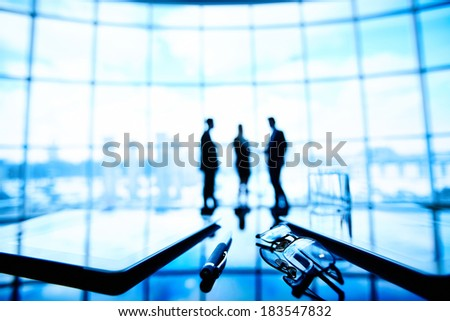 Image of eyeglasses, touchpads and pen at workplace with group of businesspeople on the background - stock photo