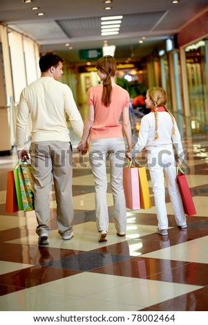 Image of family going to leave the mall after shopping - stock photo