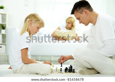 Image of father and daughter playing chess at home