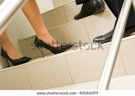 Image of female and male legs standing on marble ladder at meeting