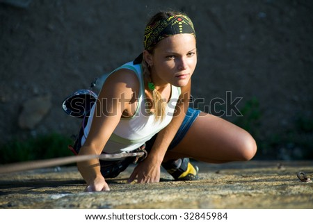 Image of female climber with rope climbing - stock photo