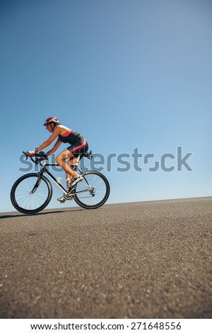 Image of female cyclist riding bicycle down hill. Athlete training for cycling event of a triathlon competition. - stock photo