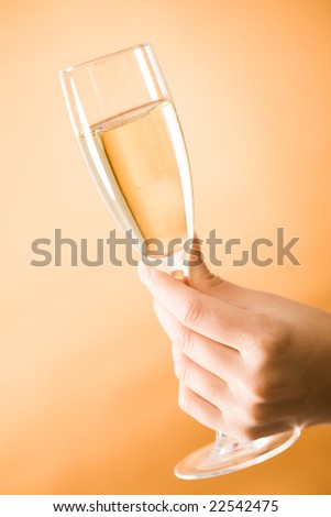 Image of female hand holding champagne on orange background