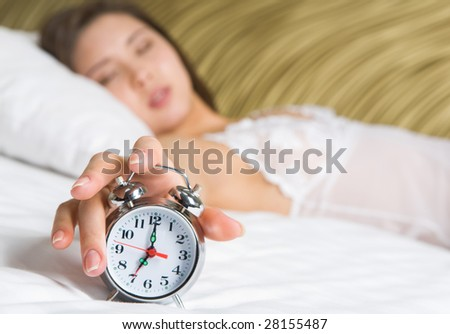Image of female hand on top of alarm clock after awakening in the morning
