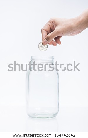 image of female hand putting a coin into glass bottle, saving concept - stock photo