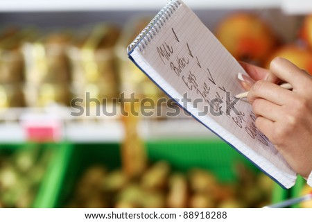 Image of female hand with pen holding product list while buying goods in supermarket - stock photo