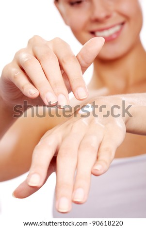 Image of female hands being treated with handcream on white background
