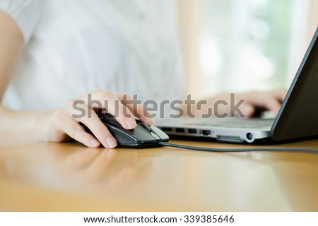 Image of female hands clicking computer mouse - stock photo