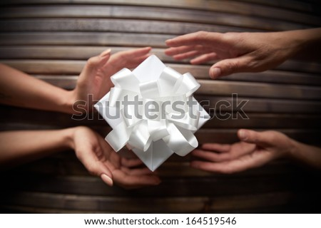 Image of female hands giving Christmas present to her friend - stock photo