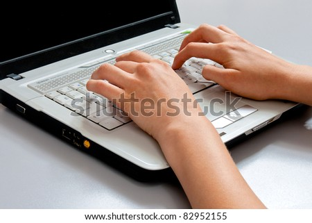 Image of female hands on the keys typing documents close-up laptop keyboard gray. top view - stock photo