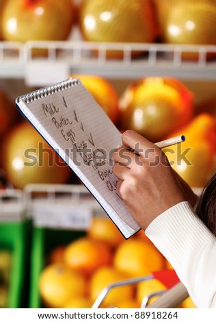 Image of female hands with pen holding product list while buying goods in supermarket - stock photo