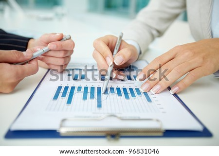 Image of female hands with pens during discussion of business documents at meeting - stock photo