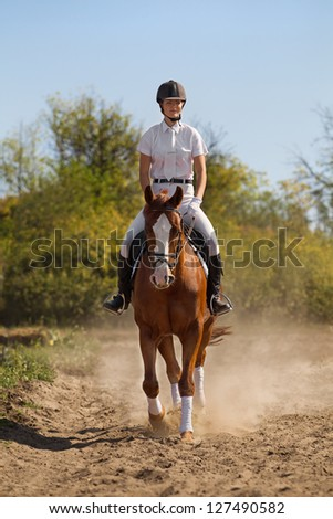 Image of female jockey with purebred horse - stock photo