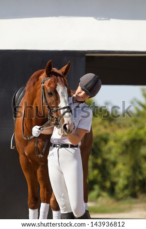 Image of  female jockey with purebred horse outdoors - stock photo