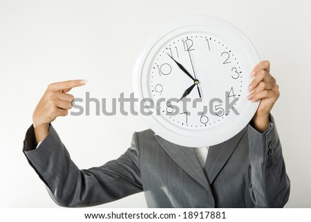 Image of female?s hands holding clock in front of face and pointing at it - stock photo