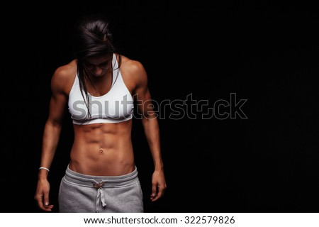 Image of fitness woman in sports clothing looking down. Young female model with muscular body. Horizontal studio shot with copy space on black background. - stock photo