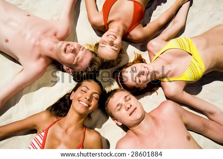 Image of five happy teens lying on the sand - stock photo