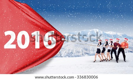 Image of five young businesspeople work together to pull a big banner with numbers 2016, shot outdoors
