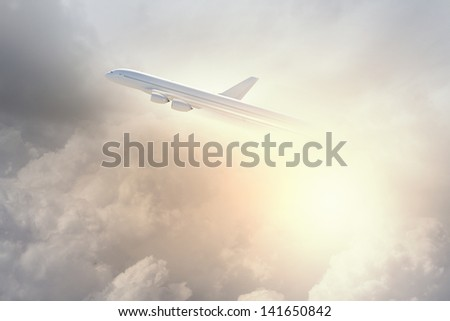 Image of flying airplane in sky with clouds at background - stock photo